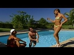Jennifer Stone shares two guys by a tropical pool.