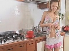 Blonde girl with amazing boobs and body posing and stripping in the kitchen