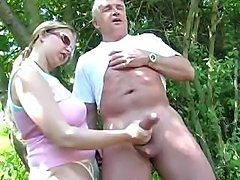 Mature couple outdoors and she gives him a handjob of the cock