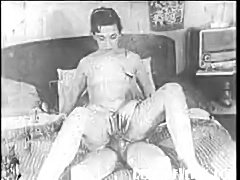 Guy spies on girl masturbating with hand and with dildo in this 1950s porn reel. He reveals himself and they commence to fucking.