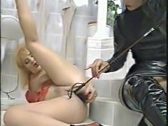 Dominatrix in black pisses on her submissive girl
